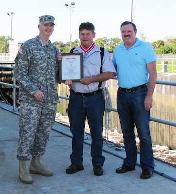 Lt. Col. Thomas Greco presented St. Lucie Lock Leader Michael L. Carter (center) with the Steel de Fleury Medal Dec. 19 at the St. Lucie Lock in Stuart, Fla. Also present was South Florida Operations Office Chief, Steve Dunham (right).