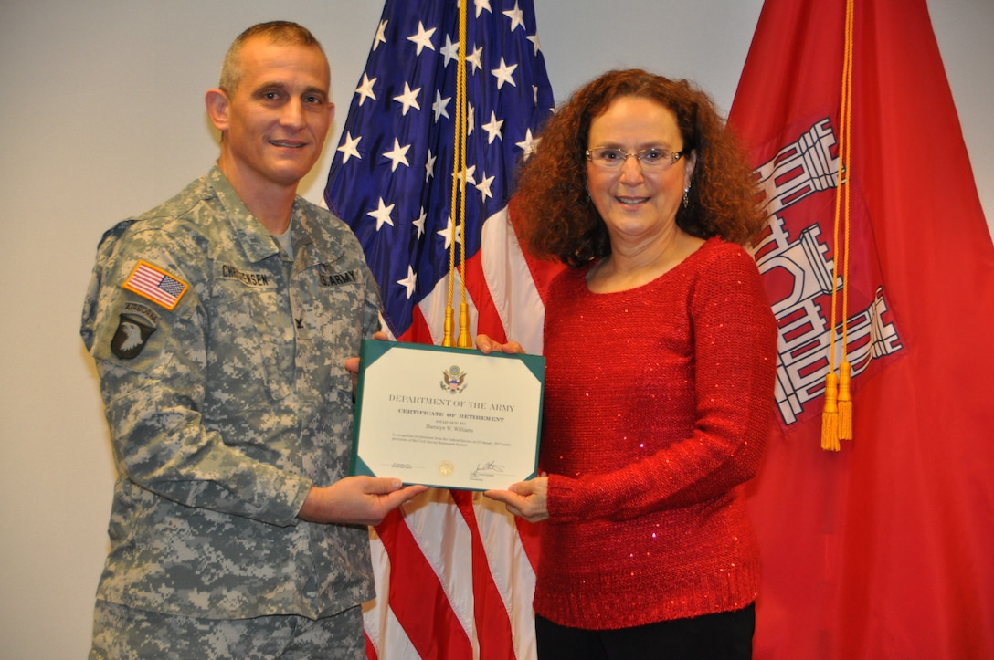 Col. Jon Christensen presents Darralyn Williams with a Certificate of Retirement at her retirement ceremony on Dec. 20.