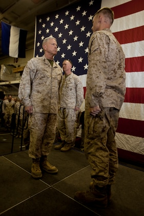 """Sergeant Royce R. Hughie (right), team leader, Scout Sniper Platoon, Battalion Landing Team 3/5, 15th Marine Expeditionary Unit, reports to Gen. James F. Amos, Commandant of the Marine Corps, before being awarded the Bronze Star with the """"V"""" combat distinguishing device in the hangar bay of the USS Peleliu, Dec. 28. Hughie received the award for his actions during 3/5's last deployment to Sangin Province, Afghanistan from 2010-2011. The CMC visited the ship to show support to the Marines and sailors of the 15th MEU and Peleliu Amphibious Ready Group during the holidays. The 15th MEU is deployed as part of the Peleliu ARG as a U.S. Central Command theater reserve force, providing support for maritime security operations and theater security cooperation efforts in the U.S. 5th Fleet area of responsibility. Hughie, 24, is from Springfield, Mo. (U.S. Marine Corps photo by Cpl. John Robbart III)"""