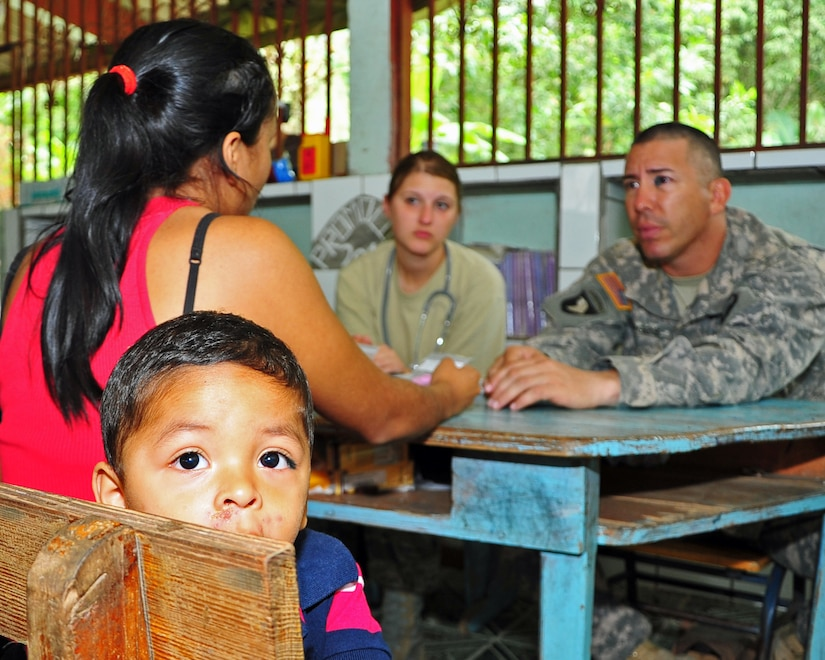OLANCHO, Honduras – A small Honduran child looks around the room while Senior Airman Sarah Shipman, Medical Element medical technician, and Sgt. Cesar Burgos, Joint Security Forces member, screen his family before sending them to a physician during a Joint Medical Readiness Training Exercise Jan. 31 here. Nurses and medical technicians evaluated approximately 1,671 during the four-day MEDRETE in the Olancho District. (Air Force photo/Staff Sgt. Bryan Franks)