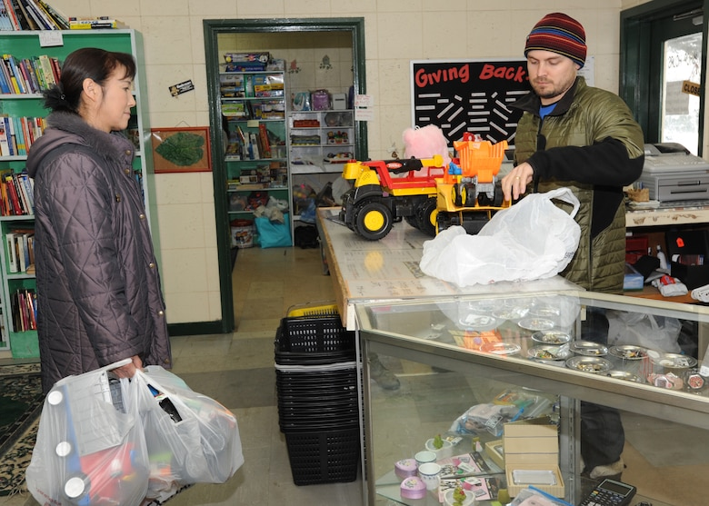 MISAWA AIR BASE, Japan – Josh Brown, Thrift Shop manager (right), checks out and bags toy trucks for a thrift shop customer here, Feb. 1. Brown has worked at the shop for 18 months, along with other paid employees and volunteers. (U.S. Air Force photo/Airman Kenna Jackson)