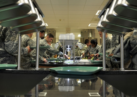 SPANGDAHLEM AIR BASE, Germany – Airmen pick up lunch trays and cutlery before proceeding to the serving line at the Mosel Dining Facility here after the facility's re-opening ceremony Feb. 1. The building closed in August 2010 for renovations to the cold-storage space, and base engineers used the facility's closure time to upgrade the serving line, foot-traffic pattern and seating area. The new appearance is designed to make meal times more efficient for DFAC customers. (U.S. Air Force photo/Staff Sgt. Daryl Knee)