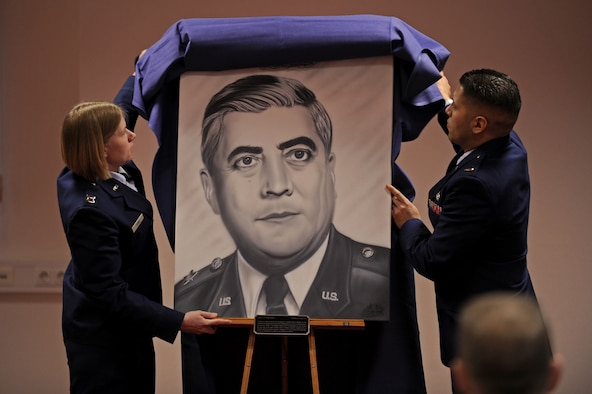 SPANGDAHLEM AIR BASE, Germany – Capt. Kristen Torma, 480th Aircraft Maintenance Unit officer in charge, left, and 2nd Lt. Jeffrey Rodriguez, 81st Aircraft Maintenance Unit assistant officer in charge, unveil a painting at a dedication ceremony in honor of Lt. Gen. Leo Marquez at the Eifel Community Center here Jan. 31. Rodriguez painted the artwork, and it will be displayed at the 52nd Maintenance Group headquarters. Airmen attended the event to honor the achievements and contributions Marquez made to the Air Force in his 33 years of service. Some of Marquez' additions include the implementation of the Air Force Combat Ammunitions Center — an advanced training course for munitions Airmen — and the maintenance badge that all Air Force maintainers now wear. Marquez died Dec. 30, 2011, at age 79.  (U.S. Air Force photo/Airman 1st Class Matthew B. Fredericks)