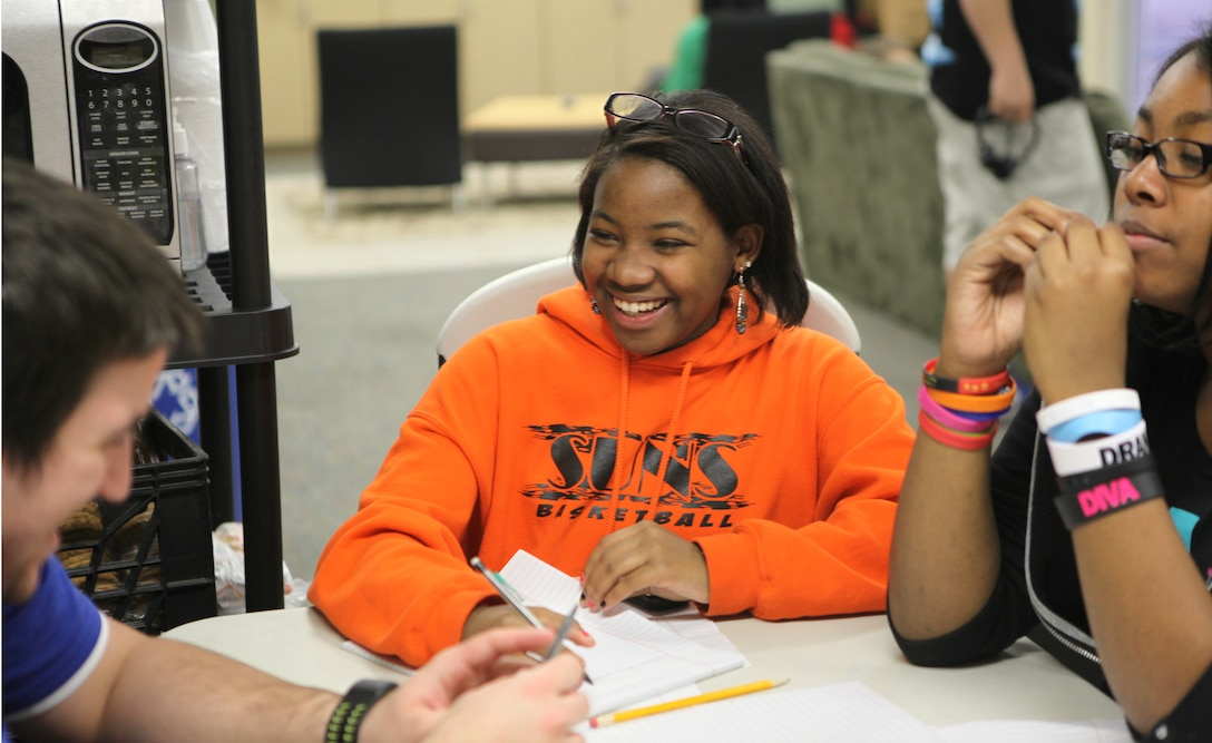 Shantrell Shae Burke, the recipient of Teen of the Month for January, laughs as she works on homework at Teen Squad at the Midway Park Community Center Feb. 3. Teen of the month is awarded through Teen Squad an after school program for teenagers aboard Marine Corps Base Camp Lejeune. Burke is an athlete and enjoys the outdoors.