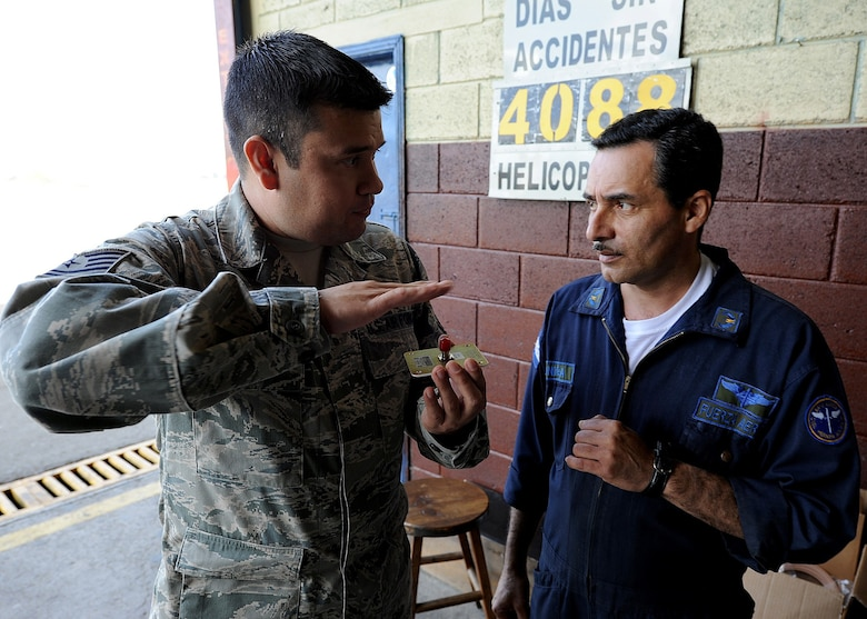 Technical Sgt. Ruben Sigala, Inter-American Air Forces Academy instructor, explains to a Honduran Air Force member the antenna placement on the helicopter tail boom, in Tegucigalpa, Honduras, Feb. 3. Sigala is one of two Airmen from IAAFA working with the 571st Mobility Support Advisory Squadron in support of a month-long Building Partner Capacity mission in Honduras.  (U.S. Air Force photo by Tech. Sgt. Lesley Waters)