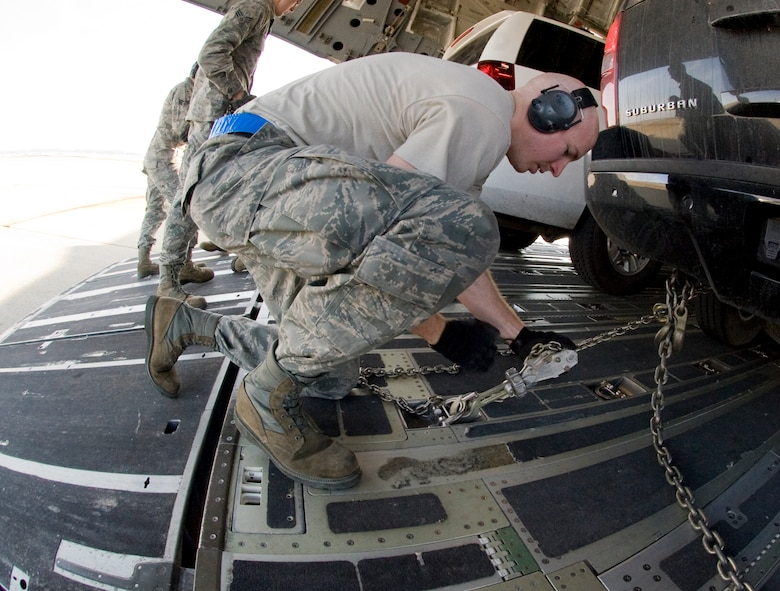 Staff Sgt. Nicholas Worrell, 89th Aerial Port Squadron aircraft services specialist, tightens down an MB-1 chain device to secure vehicles inside a            C-17 aircraft during a presidential-level mission here Jan. 25. (Photo/Bobby Jones)