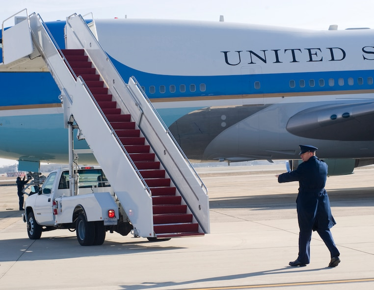 Tech. Sgt. Aubrey Lugo, 89th Aerial Port Squadron Special Air Mission Passenger (SAMPAX) service NCO in charge, spot assists a staircase truck backing away from Air Force One prior to takeoff here Jan. 25. SAMPAX provides a myriad of services in support of the 89 APS missions, such as coordinating with U.S. Secret Service to arrange security for foreign embassy representatives and distinguished visitor (D.V.) ground support. (Photo/Bobby Jones)
