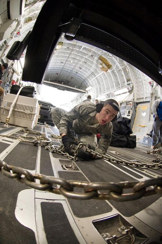 Senior Airman Michael Oniones, 89th Aerial Port Squadron aircraft services specialist, tightens down an MB-1 chain device to secure a government vehicle inside a C-17 aircraft during a presidential-level mission here Jan. 25. (Photo/Bobby Jones)