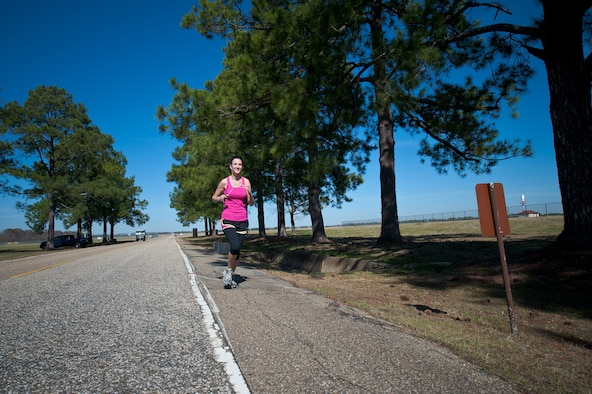 Carrie Springer, librarian with the Muir S. Fairchild Research Information Center, is one of many runners on base who run along the designated running path on March Road. The safety office advises runners to heed safety warnings posted along the running route. Runners should be cautious about sharing the road with vehicles and wear reflective gear if running at or after dawn or dusk. (Air Force photo/Melanie Rodgers Cox)