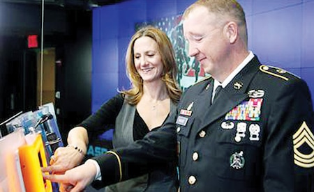 Officially closing the MarketSite, Master Sgt. Kevin Walker, operations and plans, DHHB, 1st Inf. Div., rings the NASDAQ Bell in New York City Dec. 28 with Tina Atherall, executive vice president of Hope for the Warriors.