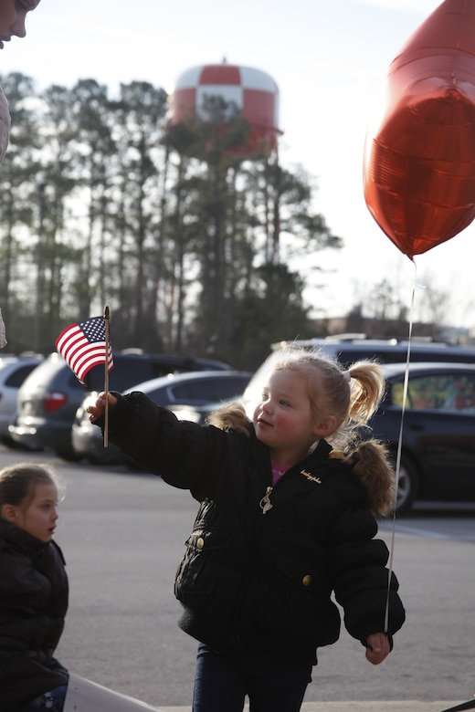 "Felicity Lizotte, 2, waves a small American flag while she waits outside the Training and Education Building for her father, Cpl. Richard Lizotte, an aviation supply specialist with Marine Aviation Logistics Squadron 14, to return Feb. 4, 2012, after a 7-month deployment to Camp Bastion, Afghanistan. ""I'm glad that we get to be a family again,"" said his wife Nicole."