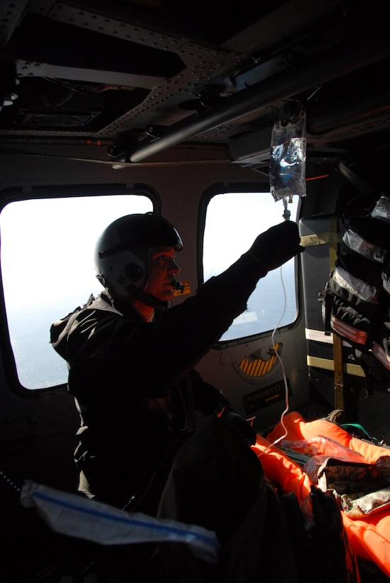 Master Sgt. Jimmy Petrolia, a pararescueman assigned to the 131st Rescue Squadron, sets up an IV drip for the patient in preparation for transport Feb. 4, 2012. Responding to the call from the Eleventh District Coast Guard at Alameda, pararescuers, or PJs, two HH-60G Pave Hawks and one MC-130P Combat Shadow aircraft departed Moffett Federal Airfield. The team provided medical assistance to a 54-year-old male who had suffered stroke-like symptoms on the MSC Beijing, acargo ship more than 200 miles off the coast of California. Guardsmen medically evacuated the patient to the San Jose Regional Medical Center. (Air National Guard photo by Senior Airman Jessica Green)