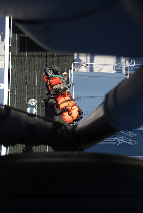 Staff Sgt. Adam Vanhaaster, a pararescueman assigned to the 131st Rescue Squadron, attached a hoist to a patients litter to be lifted into the HH-60G Pave Hawk rescue helicopter Feb. 4, 2012. Responding to the call from the Eleventh District Coast Guard at Alameda, pararescuers, or PJs, two Pave Hawks and one MC-130P Combat Shadow aircraft departed Moffett Federal Airfield. The team provided medical assistance to a 54-year-old male who had suffered stroke-like symptoms on the MSC Beijing, a cargo ship more than 200 miles off the coast of California. Guardsmen medically evacuated the patient to the San Jose Regional Medical Center. (Air National Guard photo by Senior Airman Jessica Green)