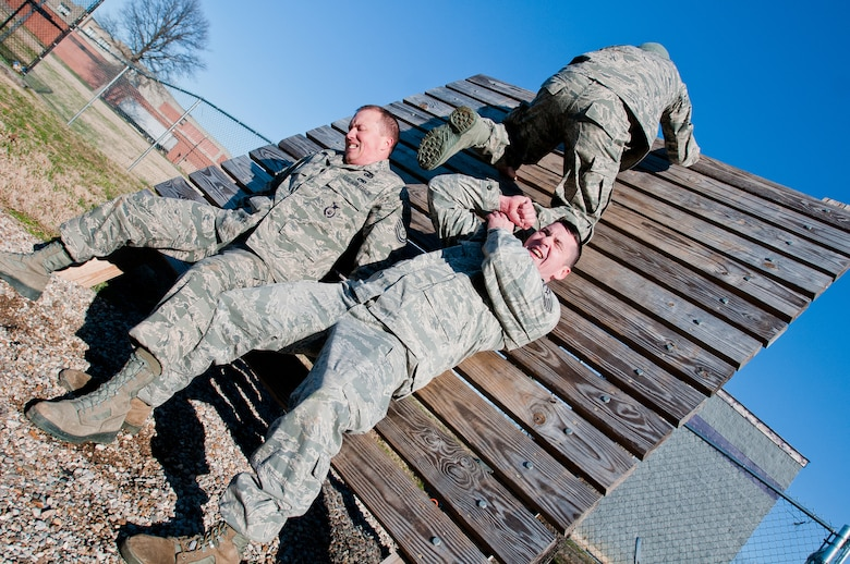 Staff Sgt. Ed Nooning and Master Sgt. Josh Devine, members of the Kentucky Air National Guard's 123rd Security Forces Squadron, help Tech. Sgt. Jesse Smith over an obstacle at Southern High School in Louisville, Ky., on Dec. 10, 2011. Airmen from the 123rd SFS were at the high school to use the Junior ROTC obstacle course for a team-building exercise as part of Wingman Day activities. (U.S. Air Force photo by Senior Airman Maxwell Rechel)