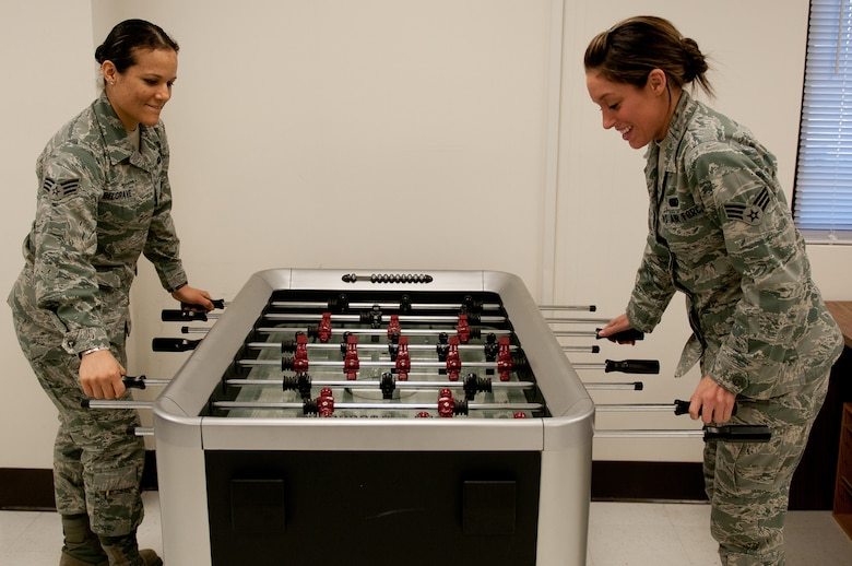 Senior Airman Jeannie Belgrave (left) and Senior Airman Ashley Nix, both food service specialists in the 123rd Force Support Squadron, play foosball at the reopening of the Kentucky Air National Guard's Morale, Welfare and Recreation facility in Louisville, Ky., on Jan. 7, 2012. The facility, now known as The Winner's Circle, also features a pool table, kitchen and volleyball court. It is operated by the 123rd Force Support Squadron. (U.S. Air Force photo by Senior Airman Maxwell Rechel)