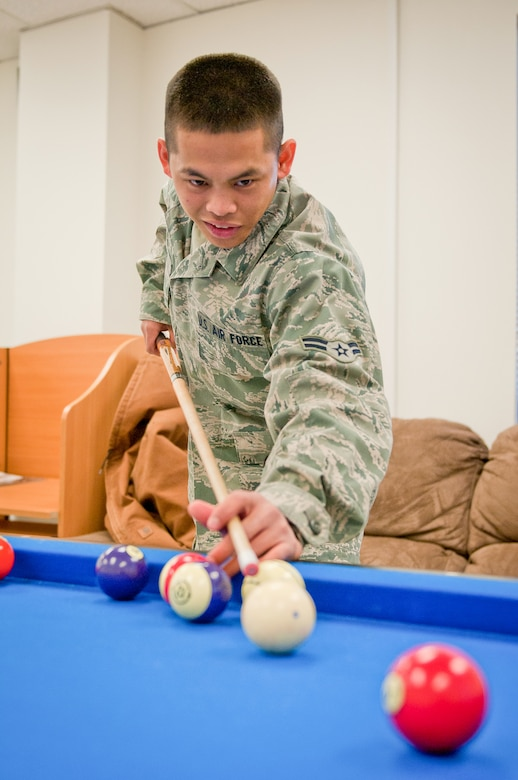 Airman 1st Class Reymart Relos, a food service specialist with the 123rd Force Support Squadron, plays pool during the reopening of the Kentucky Air National Guard's Morale, Welfare and Recreation facility in Louisville, Ky., on Jan. 7, 2012. The facility, now known as The Winner's Circle, also features a foosball table, a kitchen and a volleyball court. It is operated by the 123rd Force Support Squadron. (U.S. Air Force photo by Senior Airman Maxwell Rechel)