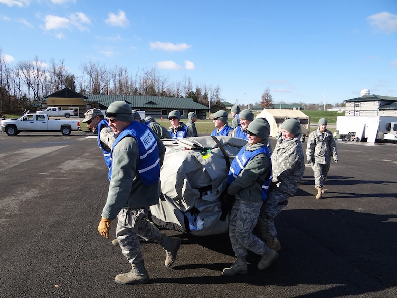 Lt. Col. David Worley (left), chief nurse of the Kentucky Air National Guard's 123rd Medical Group, leads CERFP Airmen as they position medical tents at the Wendell H. Ford Regional Training Center on Nov. 28, 2011. The CERFP is capable of  searching an incident site, rescuing and decontaminating casualties, and performing medical treatment to stabilize patients for transport to a medical facility. (Courtesy photo)