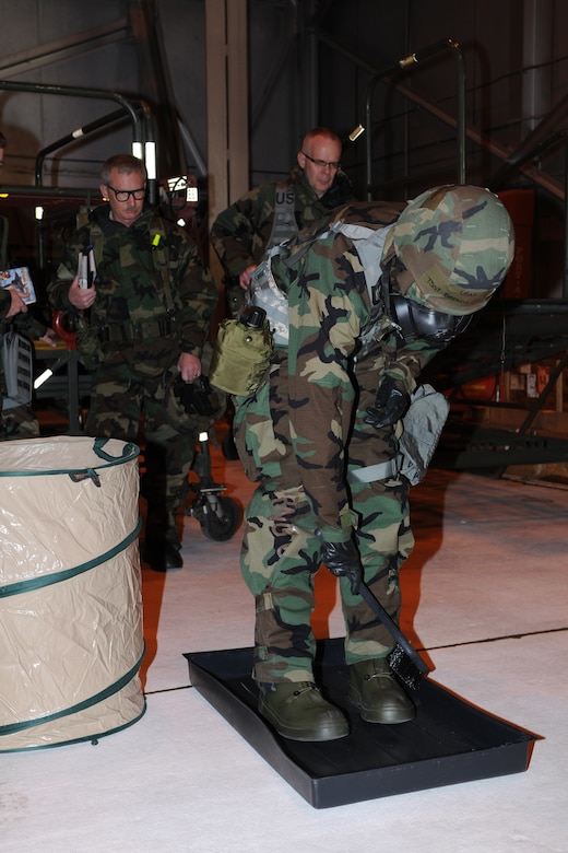 Tech. Sgt. Brenda Recksiek, 151st Logistics Readiness Squadron, demonstrates the proper way to decontaminate her overboots as part of an Ability to Survive and Operate (ATSO) exercise Feb. 4, 2012. Recksiek is wearing MOPP 4 protective gear in preparation for the 151st Air Refueling Wing's Operational Readiness Inspection in May.  (U.S. Air Force Photo by Staff Sgt. Michael Madsen/Released)