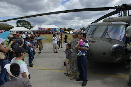 SAN SALVADOR, El Salvador - Army 1st Lt. Jimmy Cogles, a 1st Battalion, 228th Aviation Regiment pilot, poses for pictures during the annual Ilopango Air Show at Ilopango International Airport last month.  Members of the battalion and the 612th Air Base Squadron represented Joint Task Force-Bravo, Soto Cano Air Base, Honduras, at the 2012 air show. Airmen and Soldiers were on hand to answer questions and pose for pictures as an estimated 35,000 people enjoyed the sights, sounds, and smells at one of the largest air shows in Central America. (Air Force photo/Lt. Col. Lloyd Malone)