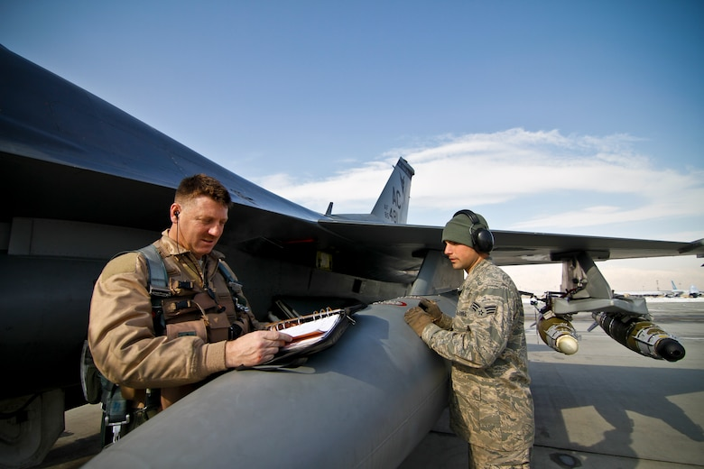 U.S. Air Force Lt. Col. Bradford Everman, an F-16C Fighting Falcon pilot, does a pre-flight briefing with Airman First Class Jeffrey Montemurro, an F-16C crew chief, on Feb 5, 2012 at Bagram Airfield, Afghanistan.  Everman is the commander of the 119th Expeditionary Fighter Squadron, and Montemurro is assigned to the 455th Expeditionary Aircraft Maintenance Squadron.  Both are deployed from the 177th Fighter Wing, New Jersey Air National Guard, which is located at Atlantic City International Airport, NJ.  The 177th is deployed to provide close air support to coalition forces.  U.S. Air Force photo/Tech. Sgt. Matt Hecht