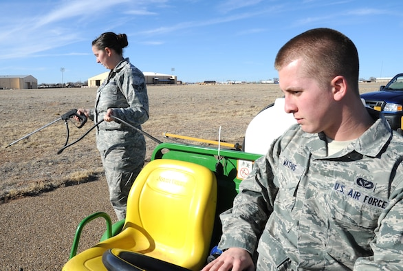 U.S. Air Force Senior Airman C?Belle Tennimon sprays weed killer while Airman 1st Class Jacob Mathis navigates their vehicle near the flightline at Cannon Air Force Base, N.M., Feb. 1, 2012. Both Air Commandos are pest managers who routinely deal with public health concerns at Cannon. (U.S. Air Force photo by Airman 1st Class Alexxis Pons Abascal)