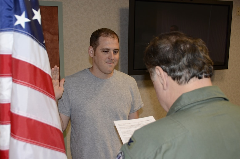 Tech. Sgt. Jason Cosgrave, 144th Medical Group, gets sworn in by Col. Joseph Pascuzzo, 144th Medical Group Commander, 144th Fighter Wing, after almost a year of being seperated from the very same unit.  Cosgrave overcame some personal adversities and was able to re-enlist into his former unit on January 31, 2012.  (Air National Guard photo by Senior Master Sgt. Chris Drudge)