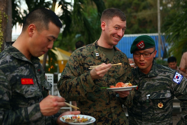 Capt. Andrew Reaves, the fires officer for the 31st Marine Expeditionary Unit, enjoys some Pad Thai with his Republic of Korea Marine counterparts during an icebreaker event, Feb. 8. The event was conducted as part of Exercise Cobra Gold 2012 to introduce multinational service members to Thailand. CG 2012 demonstrates the resolve of the U.S. and participating nations to increase interoperability and promote security and peace throughout the Asia-Pacific region. The 31st MEU is the U.S.'s expeditionary force in readiness in the Asia-Pacific region.
