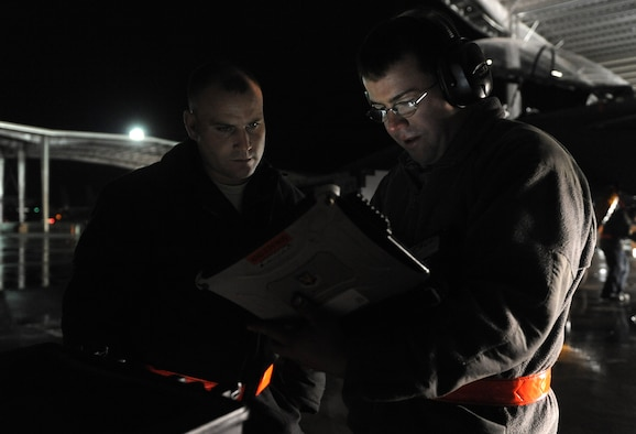 U.S. Air Force Staff Sgts. Austin Mauch and Randy Drake, 391st Aircraft Maintenance Unit dedicated crew chiefs, consult a technical order before performing maintenance on an F-15E Strike Eagle Feb. 1, 2012 at Mountain Home Air Force Base, Idaho. Crew chiefs are constantly inspecting aircraft ensuring every part is fully operational. (U.S. Air Force photo by Debbie Lockhart/Released)