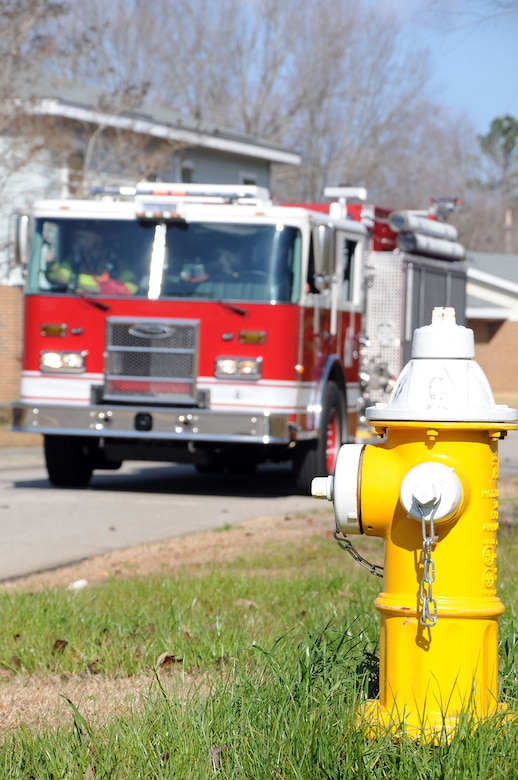 Firefighters from the 628th Civil Engineer Squadron, Civil Engineer Fire Department's Station Six, respond to a simulated fire at a home in the MenRiv Housing area at Joint Base Charleston - Weapons Station during an exercise Feb. 2.  The first fire truck to report on scene is required to be in position within four to seven minutes of the emergency call. A second truck arrives on the scene within seven to 10 minutes to assist the first truck. (U.S. Navy photo/Petty Officer 1st Class Jennifer Hudson)