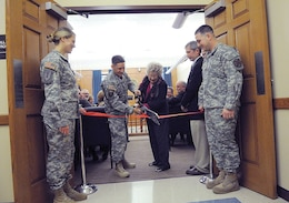 Lt. Col. John Hamner, 1st Inf. Div. deputy SJA, and Sharon Reid, widow of Judge John Thomas Reid, cut the ribbon during a dedication ceremony for a courtroom in Clausen Hall. It was named in honor of Reid's husband, the late Honorable John Thomas Reid, a Kansas district judge who presided over cases at Fort Riley for 17 years.