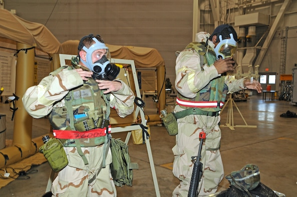 National Guard Senior Airman Farris Floyd and National Guard Tech. Sgt. Anthony Fields don their MCU-2 protective masks during a simulated chemical attack at Gulfport Combat Readiness Training Center, MS., Feb. 2, 2012. As part of the Air Mobility Command's Operational Readiness Inspection, Floyd and Fields must show they are able to survive and operate in a chemical environment by donning their chemical ensemble.  (National Guard photo by Staff Sgt. Noel Velez Crespo /released).