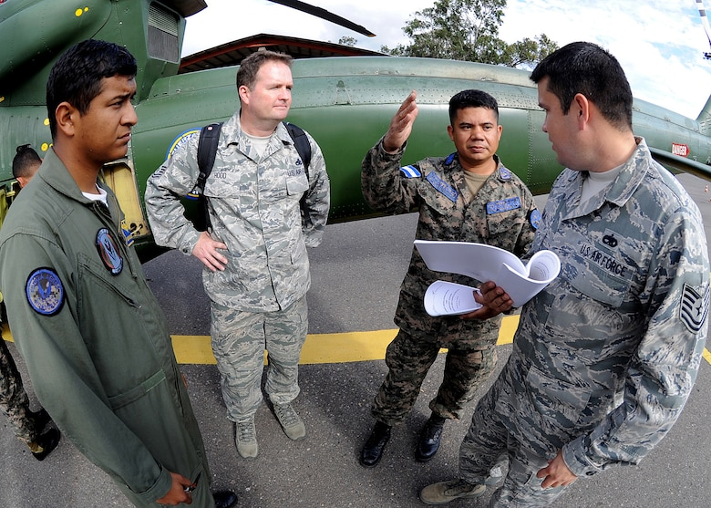 Honduran Air Force Sub-official Master 1st Class Juan Carlos Rodriguez Rivas, helicopter flying crew chief, and Senior Master Sgt. Jason Hood, 571st Mobility Support Advisory Squadron helicopter crew chief and air advisor, listens in as FAH Sub-official Master 2nd Class Enrique Hernandez Sanchez, FAH inspector, and Technical Sgt. Ruben Sigala, Inter-American Air Forces Academy instructor, discusses the inflight operational check of the radar altimeter system at Col. Hernán Acosta Mejia Air Base, Tegucigalpa, Honduras, Feb. 6.  (U.S. Photo by Tech. Sgt. Lesley Waters)