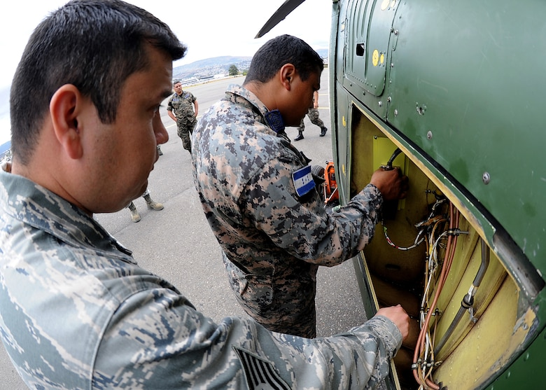 Technical Sgt. Ruben Sigala, Inter-American Air Forces Academy instructor, 318th Training Squadron, Lackland AFB, Texas, looks on as Honduran Air Force Sergeant Major Fernando David Fonseca, aircraft electrician, makes final wiring adjustments during the installation of the radar altimeter at Col. Hernán Acosta Mejia Air Base, Tegucigalpa, Honduras, Feb. 6.  (U.S. Photo by Tech. Sgt. Lesley Waters)