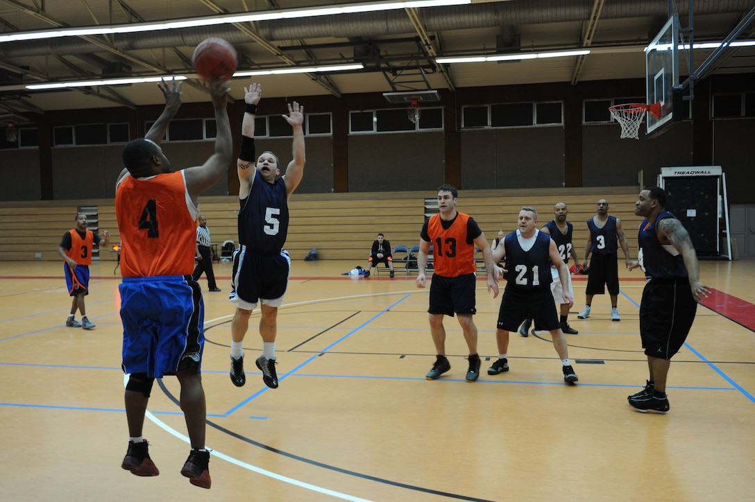SPANGDAHLEM AIR BASE, Germany - Aloysius Moore, 52nd Medical Group, shoots a three point shot over Mark Dewitz, 726th Air Mobility Squadron, during an over-30 basketball league playoff game at the Skelton Memorial Fitness Center here Feb. 7. The 726th AMS team rose to victory against the 52nd MDG with a final score of 37-27. The league championship game will take place Feb. 13 at the fitness center. (U.S. Air Force photo by Senior Airman Christopher Toon/Released)