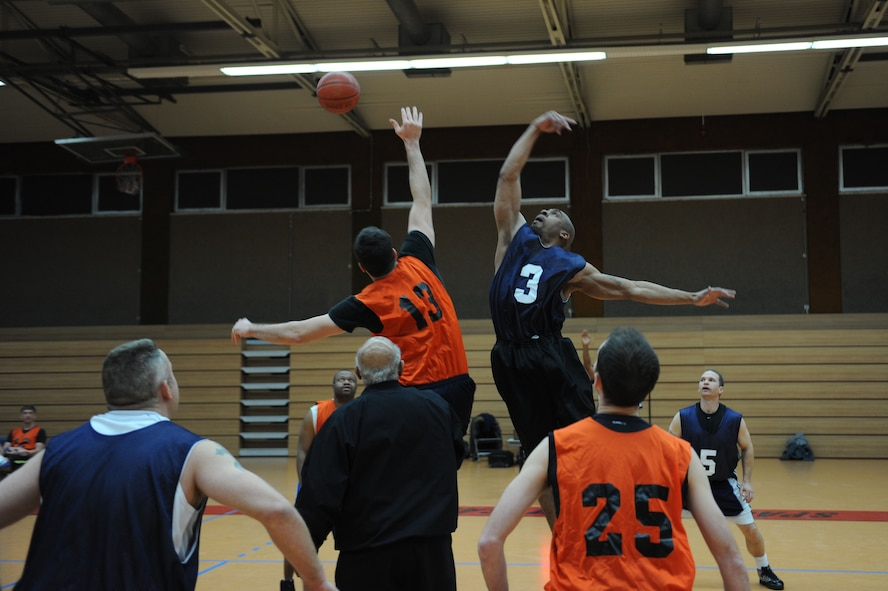 SPANGDAHLEM AIR BASE, Germany –(L to R) Brandon Pieper, 52nd Medical Group, and Tommie Albright, 726th Air Mobility Squadron, jump for the ball during the opening tip-off of an over-30 basketball league playoff game at the Skelton Memorial Fitness Center here Feb. 7. The 726th AMS team rose to victory against the 52nd MDG with a final score of 37-27. The league championship game will take place Feb. 13 at the fitness center. (U.S. Air Force photo by Senior Airman Christopher Toon/Released)