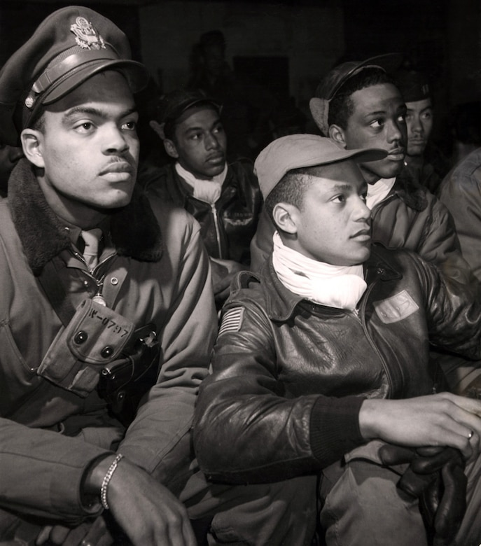 Airmen of the 332nd, from left to right: Robert W. Williams, William H. Holloman, Ronald W. Reeves, Christopher W. Newman and Walter M. Downs listen to a briefing in March 1945.  Photo by Toni Frissell, Library of Congress.