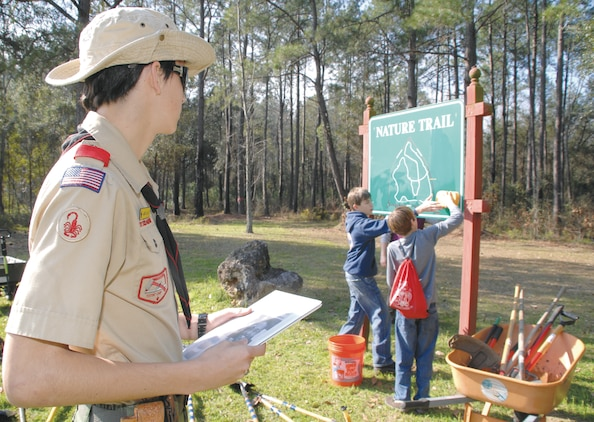 Jared R. Gillan observes Boy Scouts as they clean the sign at the nature trail's entrance, Feb. 4.