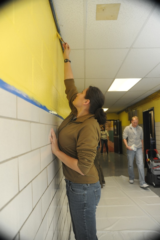 WASHINGTON -- Staff Sgt. Brittinie Alvarez, a member of the newly-formed 11th Wing Commander's Action Group, paints the main entrance hallway at C.W. Harris Elementary School Feb. 4. Military personnel from the National Capitol Region and their families helped spruce up the school by painting the hallways and all of the doors, power-washing the exterior, removing grafitti and setting up classrooms.  (U.S. Air Force photo/Senior Airman Amber Russell)