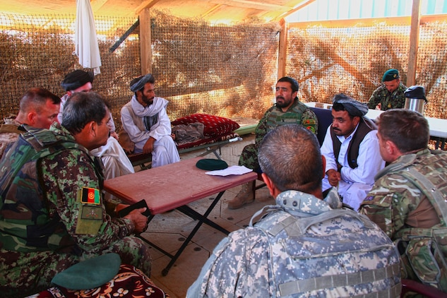 Afghan National Army troops from the 215th Corps and local Washir district, Helmand province, government officials sit down during a shura with local Afghans in the district, August 19. During the shura the Afghans talked about local crime and putting an end to it.
