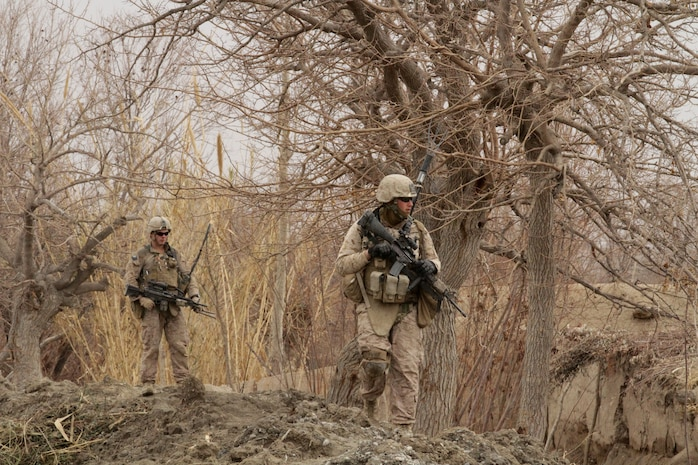 Lance Cpl. Dakota M. Landrie (left), an automatic rifleman with India Company, 3rd Battalion, 7th Marine Regiment, and Lance Cpl. William M. Baldridge (right), a radio operator with, India Co., patrol here recently. Landrie, a 19-year-old native of Indian Land, S.C., and 2010 graduate of Indian Land High School, and Baldridge, a 22-year-old native of Palmdale, Calif., traversed steep terrain to take a new route to the surrounding farmland.