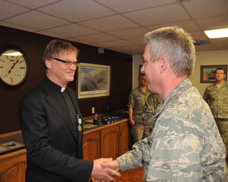 Col. Michael Mayo of the 128th Air Refueling Wing congratulates Chaplain Christopher Myers after presenting him with the Army Accommodation Medal. Chaplain Myers earned the Accommodation Medal while stationed at Landstuhl Regional Medical Center in Germany.