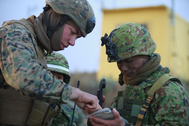 Lance Cpl. Joseph A. Ferguson, fire support man, 1st Air Naval Gunfire Liaison Company, shows a Japanese soldier the information needed to request close air support during a combined arms exercise with the Japanese Ground Self Defense Force, Feb. 12. The exercise included 81 and 120mm mortars, fixed and rotary wing assets and Naval gun fire.  In addition to the gunfire exercise, the Japanese also practiced calling for fire. Exercise Iron Fist 2012 is a bilateral training exercise that gave the 15th MEU a chance to demonstrate its amphibious capabilities to the Japanese. Ferguson, 19, is from Brentwood, Calif.