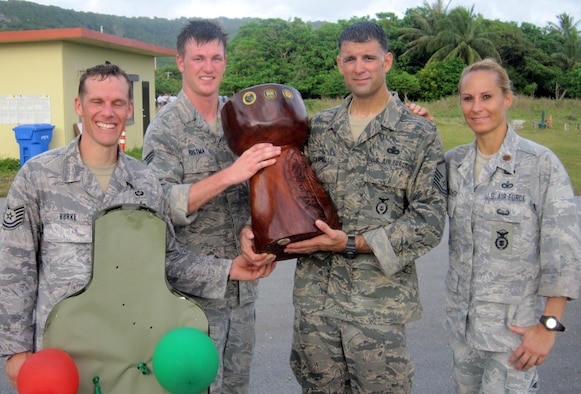 Competitors from the 736th Security Forces Squadron (from left, Tech. Sgt. Vance Burke, Senior Airman Evan Postma, Master Sgt. Seth Campbell and Maj. Tara Opielowski) pose with the coveted latte stone trophy at the combat arms training and maintenance range after claiming victory during the 36th Contingency Response Group's quarterly warrior day competition here Feb. 6. (U.S. Air Force courtesy photo)