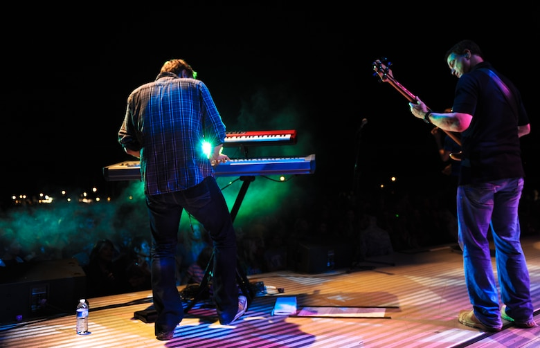"""Ben Lewis and Gary Sinise, members of the Lt. Dan Band, perform a concert for the troops Feb. 10 at Joint Base Pearl Harbor-Hickam, Hawaii. The band closed the show with """"Proud to be an American."""" The crowd sang along and held up their lighters throughout the song. (U.S. Air Force photo/Senior Airman Lauren Main)"""