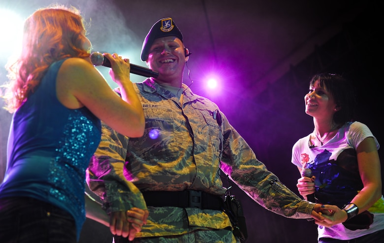 Julie Dutchak and Molly Callinan, vocalists with the Lt. Dan Band, serenade Staff Sgt. Jonathan Bielke, a military working dog handler with the 647th Security Forces Squadron, during the Lt. Dan Band concert Feb. 10 at Joint Base Pearl Harbor-Hickam, Hawaii. Bielke was standing at the front of the stage providing security when the singers pulled him on stage to sing a ballad by Aretha Franklin. (U.S. Air Force photo/Senior Airman Lauren Main)