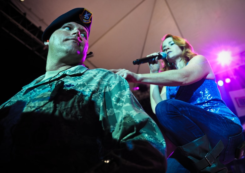 """Julie Dutchak, a vocalist with the Lt. Dan Band, taps Staff Sgt. Jonathan Bielke, military working dog handler with the 647th Security Forces Squadron, to bring him on stage for a song during the Lt. Dan Band concert Feb. 10 at Joint Base Pearl Harbor-Hickam, Hawaii. Dutchak pulled Bielke on stage and sang """"Natural Woman"""" by Aretha Franklin. (U.S. Air Force photo/Senior Airman Lauren Main)"""