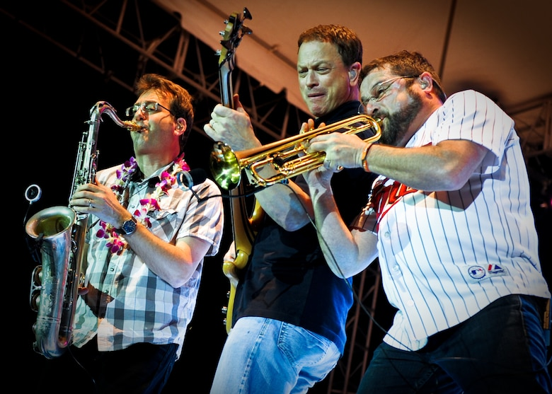 """Mitch Paliga, Gary Sinese and Kirk Garriso, members of the Lt. Dan Band, perform a concert for the troops Feb. 10 at Joint Base Pearl Harbor-Hickam, Hawaii. The Lt. Dan Band derives its name from the character Sinise played in the 1994 film """"Forrest Gump."""" (U.S. Air Force photo/Senior Airman Lauren Main)"""