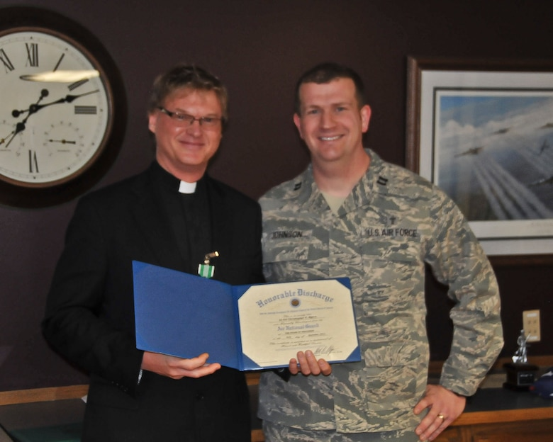 Chaplain Ben Johnson of the 128th Air Refueling Wing presents Chaplain Christopher Myers with his Honorable Discharge after 26 years of military service.