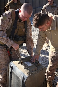 CAMP LEATHERNECK, Afghanistan-Cpl. Samuel Stark, radio operator, 1st Brigade, 5th Air Naval Gunfire Liaison Company (left), and Cpl. Hunter A. St Cyr, forward observer, 1st Brigade, 5th ANGLICO (right), unload their deployment bags aboard Patrol Base Hazrat, Nov. 28. The 5th ANGLICO took over 1st ANGLICO's area of operations, Dec. 4 after weeks of receiving briefs from 1st ANGLICO on the mission, successes and concerns in the area.