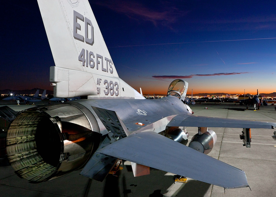 With the night lights of downtown Las Vegas and F-15s from the Republic of Korea Air Force serving as a backdrop, an F-16 from the 416th Flight Test Squadron awaits for its aircrew to prep the aircraft for a night sortie during Red Flag Jan. 25. (Lockheed Martin photo by Chad Bellay)